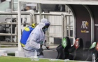 A worker disinfects the stadium after the match. REUTERS/FILE