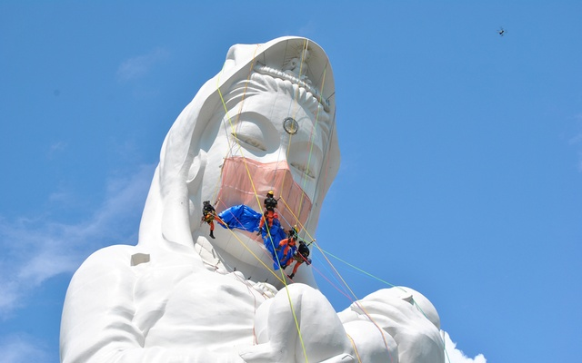 Workers place a mask on a 57-metre-high statue of Buddhist goddess Kannon to pray for the end of the coronavirus disease (COVID-19) pandemic at Houkokuji Aizu Betsuin temple in Aizuwakamatsu, Fukushima Prefecture, Japan in this handout photo taken on June 15 2021. REUTERS