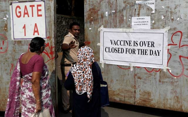 A policeman asks people who came to receive a dose of a coronavirus vaccine to leave as they stand outside the gate of a vaccination centre which was closed due to unavailability of the supply of COVID-19 vaccine, in Mumbai, India. REUTERS