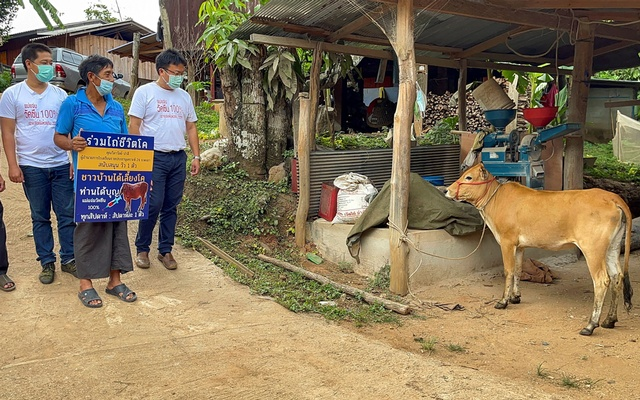 Charan Damrongkiatpana holds up a sign after winning a raffle campaign for inoculated residents to win a live cow per week, in a bid to boost the local the coronavirus disease (COVID-19) vaccination drive in Chiang Mai province, Thailand, June 8, 2021. REUTERS