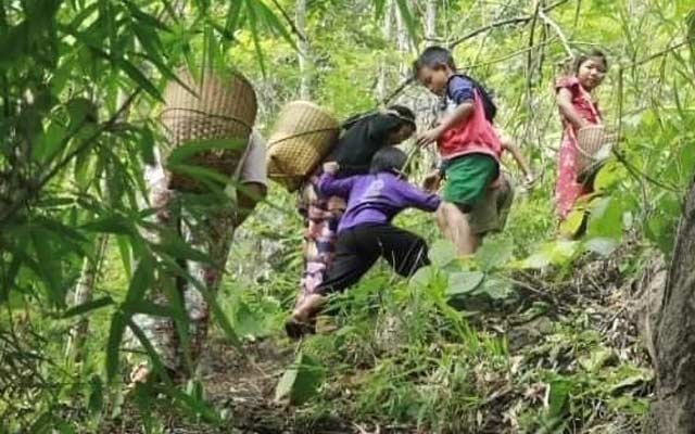 People displaced by fighting in eastern Myanmar climb through forest in Kayah State, May 26, 2021. REUTERS