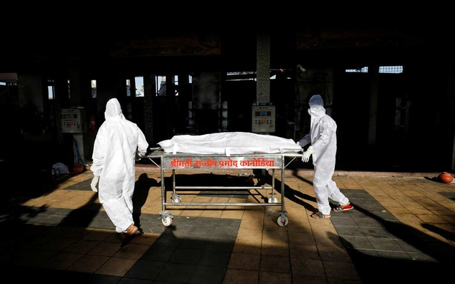 Workers move the body of a person who died from the coronavirus disease (COVID-19) for cremation inside the Kurukshetra crematorium in Surat, India, May 11, 2021. REUTERS