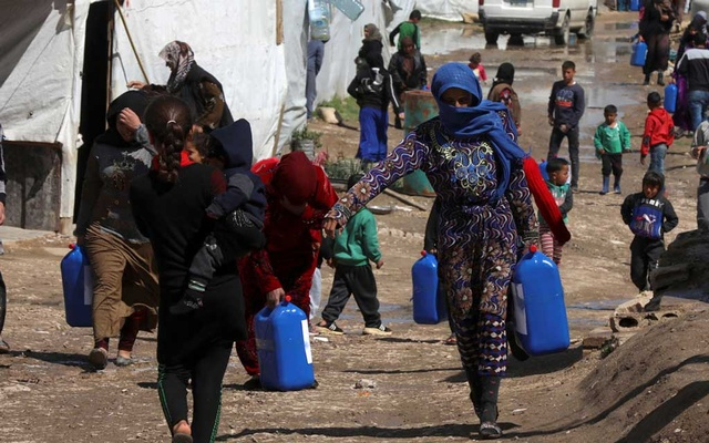Syrian refugees walk as they carry containers at an informal tented settlement in the Bekaa valley, Lebanon March 12, 2021. Reuters