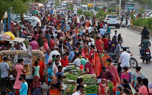 People shop at a crowded roadside vegetable market after authorities eased coronavirus restrictions, following a drop in COVID-19 cases in Ahmedabad, India, Jun 15, 2021. REUTERS