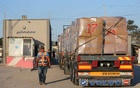 A Palestinian man stands next to a truck carrying clothes for export, at Kerem Shalom crossing in Rafah in the southern Gaza Strip, Jun 21, 2021. REUTERS