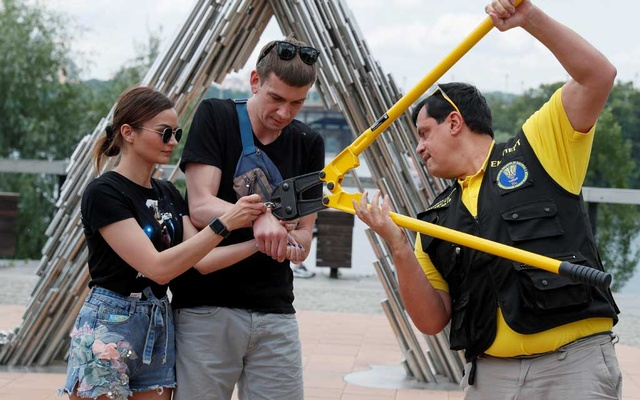 Alexandr Kudlay and Viktoria Pustovitova, who handcuffed themselves and spent 123 days together, have the chain dismantled by a representative from a Ukrainian record book in Kyiv, Ukraine June 17, 2021. REUTERS