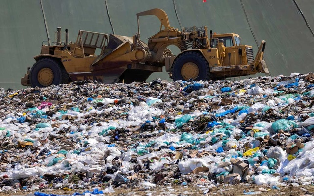 Workers use heavy machinery to move trash and waste at the Frank R Bowerman landfill on Irvine, California, US, June 15, 2021
