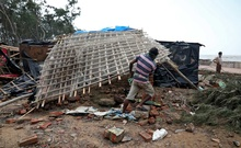 A man removes bamboo rooftop of a damaged hut following Cyclone Yaas in Digha, Purba Medinipur district, in the eastern state of West Bengal, India, May 27, 2021. REUTERS/Rupak De Chowdhuri