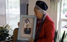 Rebiya Kadeer, 74, holds a framed photo of her imprisoned son at her home in Fairfax, Va, on May 28, 2021. A Uyghur activist, Kadeer has been living in exile in the United States since 2005. (Jared Soares/The New York Times)