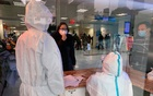 Hospital personnel wearing protective medical gowns speak to a woman at No. 5 Hospital in Wuhan, China on Jan. 24, 2020. The New York Times