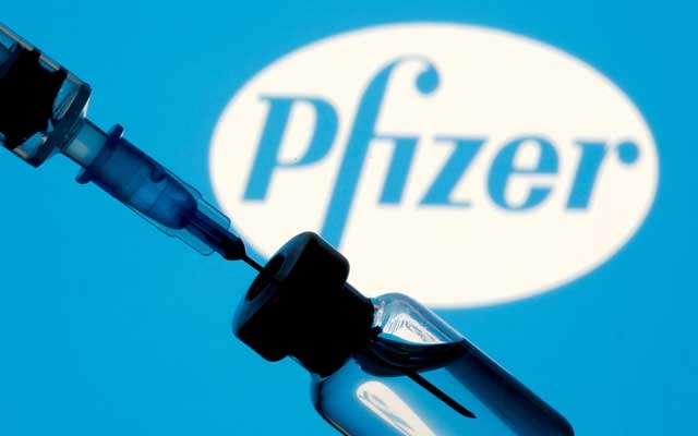 A vial and syringe are seen in front of a displayed Pfizer logo in this illustration taken Jan 11, 2021. REUTERS