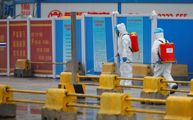 Workers in PPE spray the ground with diinfectant in Baishazhou market during a visit of World Health Organization (WHO) team tasked with investigating the origins of the coronavirus (COVID-19) pandemic, in Wuhan, Hubei province, China, January 31, 2021. REUTERS