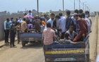 The police stop a pickup carrying passengers while another passes by a check-post at Gabtoli on Friday, Jun 25, 2021 amid a shutdown of long-haul passenger transport from the city. Photo: Asif Mahmud Ove