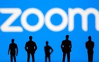 Small toy figures are seen in front of Zoom logo in this illustration picture taken Mar 15, 2021. REUTERS