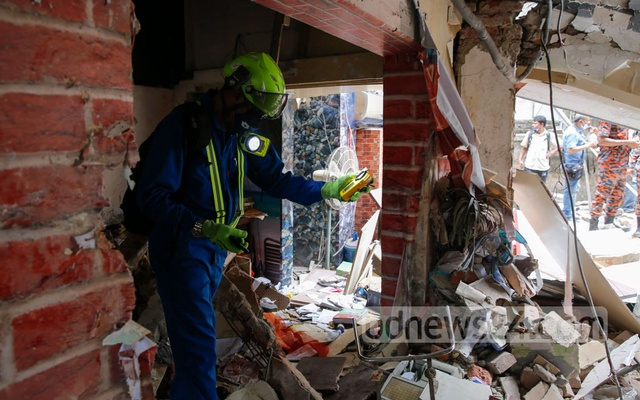 A probe committee member conducts a test to determine the presence of methane gas at the explosion site in Dhaka's Moghbazar on Monday, Jun 28, 2021. Photo: Mahmud Zaman Ovi