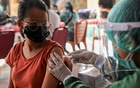 A woman receives a dose of AstraZeneca COVID-19 vaccine during a mass vaccination programme for Green Zone Tourism in Sanur, Bali, Indonesia, March 23, 2021. REUTERS