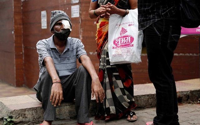Shivaji Veer, 51, a school bus driver, accompanied by his wife Vimal Veer 46, waits to board a taxi to go home after a follow-up consultation at a hospital after losing his eye due to Mucormycosis, also known as black fungus, in Pune, India, Jul 1, 2021. REUTERS