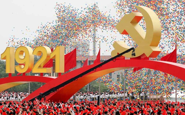 Participants wave national and party flags as balloons are released at the end of the event marking the 100th founding anniversary of the Communist Party of China, on Tiananmen Square in Beijing, China Jul 1, 2021. REUTERS