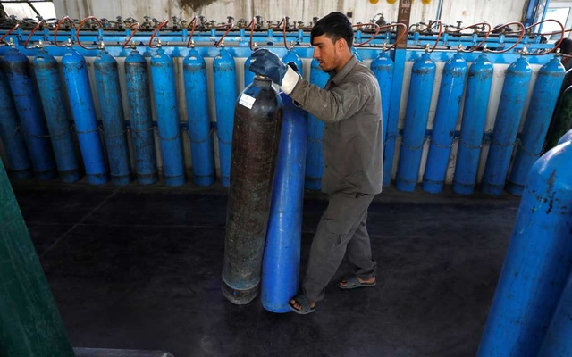 A worker carries two oxygen cylinders at the factory, amid the spread of the coronavirus disease (COVID-19), in Kabul, Afghanistan June 15, 2021. REUTERS/Stringer