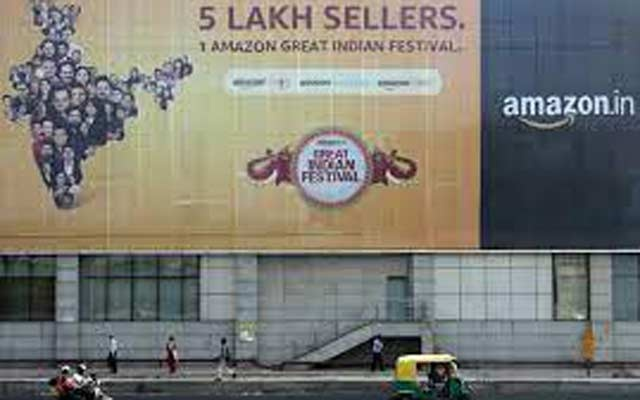 People move past a hoarding of Amazon India outside a metro rail station in New Delhi, India, October 23, 2019. REUTERS