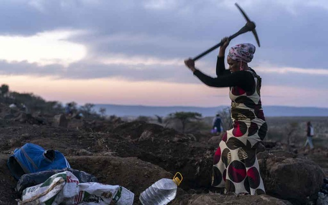 A woman digs for precious stones in KwaHlathi, South Africa, June 17, 2021. The New York Times