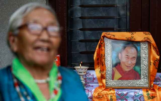 A Tibetan woman dressed in traditional attire stands near the portrait of Dalai Lama during a function organised to mark the 86th birthday celebration of Dalai Lama in Lalitpur, Nepal, July 6, 2021. REUTERS