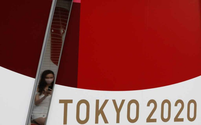 A woman wearing a protective mask, following the coronavirus disease (COVID-19) outbreak, is reflected on a metal bar on an advertisement for Tokyo 2020 Olympic Games in Tokyo, Japan, July 7, 2021. REUTERS