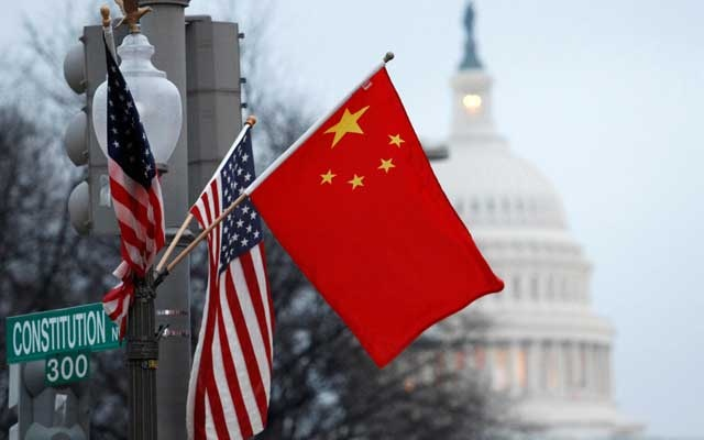 The People's Republic of China flag and the US flag fly on a lamp post along Pennsylvania Avenue near the US Capitol in Washington during then-Chinese President Hu Jintao's state visit, January 18, 2011. REUTERS