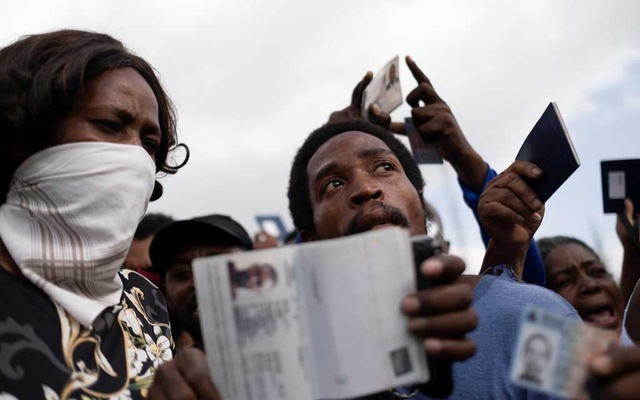 Haitians asking for asylum hold up their Haitian passports in front of the US embassy, following the assassination of President Jovenel Moise, in Port-au-Prince, Haiti Jul 9, 2021. REUTERS