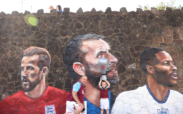 Football - England fans pose for a photograph in front of a giant mural created by street artist Nathan Parker of Gareth Southgate, Harry Kane and Raheem Sterling ahead of the Euro 2020 final against Italy - Bullring, Nuneaton, Britain - July 10, 2021 Action Images via Reuters/Lee Smith