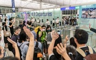 Travelers wave goodbye to friends and family at the Hong Kong International Airport, June 24, 2021. In the year since China imposed a sweeping national security law on its territory of Hong Kong, a former British colony, tens of thousands of people have made plans to leave the city. (Anthony Kwan/The New York Times)