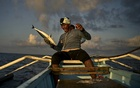 A fisherman off the coast of Bani, the Philippines, May 29, 2021. The New York Times.
