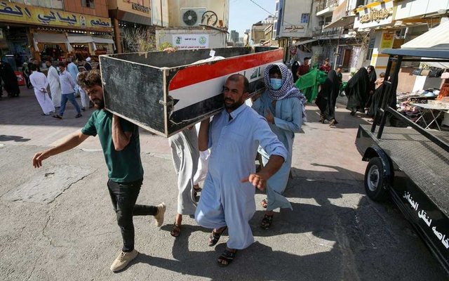 Mourners carry the coffin of a victim, who was killed in a fire that broke out at al-Hussain coronavirus hospital in Nassiriya, during a funeral in Najaf, Iraq, July 13, 2021. REUTERS/Alaa Al-Marjani