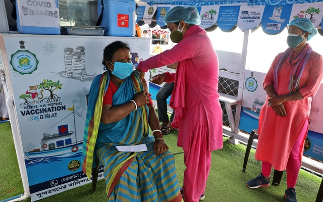 Angurbala Kamila, 45, a villager, receives a dose of COVISHIELD vaccine, a coronavirus disease (COVID-19) vaccine manufactured by Serum Institute of India, on a boat during