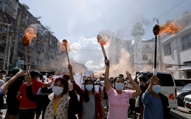 A group of women hold torches as they protest against the military coup in Yangon, Myanmar July 14, 2021. REUTERS