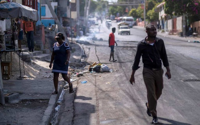 People walk on a street after tires were set on fire by protesters upset with growing violence in the Lalue neighbourhood, a week after the assassination of President Jovenel Moise, in Port-au-Prince, Haiti July 14, 2021. Reuters