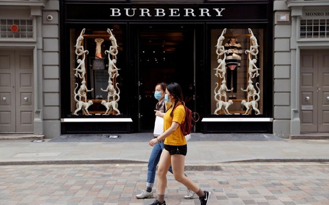 People wearing protective masks walk past a Burberry store at Covent Garden, in London, Britain June 15, 2020. REUTERS