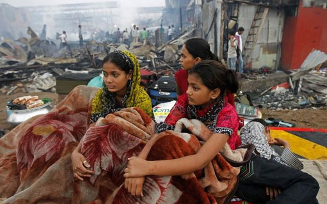 Rubina Ali, who acted as young Latika in the Oscar-winning film Slumdog Millionaire, sits with her family amid the ruins of the Gharib Nagar slum. A fire gutted the slum, a large shanty town which was home to thousands of residents next to the Bandra railway station, northwest Mumbai.