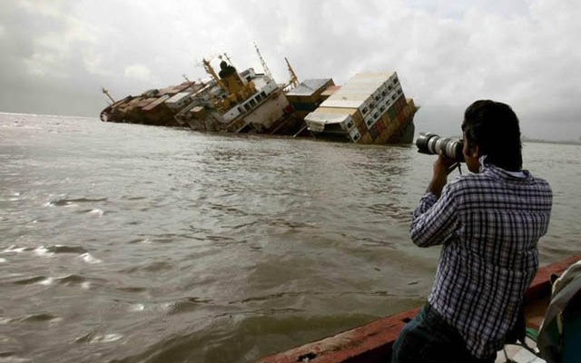 Reuters photographer Danish Siddiqui takes pictures from a fishing boat of the damaged cargo ship MSC Chitra in the Arabian Sea off the Mumbai coast.