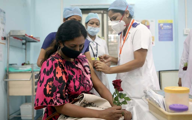 A healthcare worker holding a rose is vaccinated against COVID-19 at a medical centre in Mumbai, India, Jan 16, 2021. REUTERS