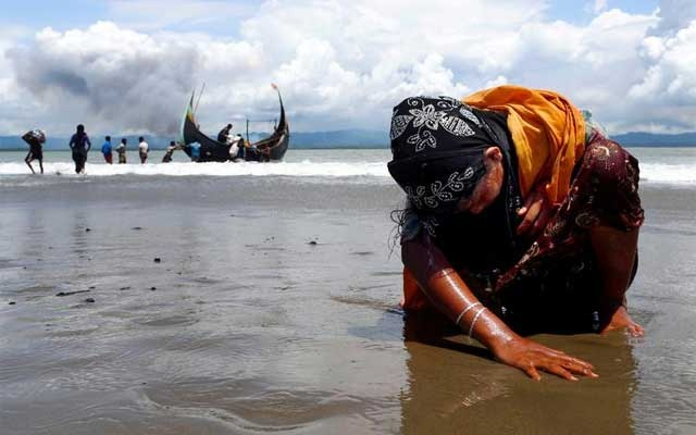 An exhausted Rohingya refugee woman touches the shore after crossing the Bangladesh-Myanmar border by boat through the Bay of Bengal, in Shah Porir Dwip, Bangladesh Sept 11, 2017. REUTERS/Danish Siddiqui