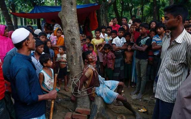 A man accused of stealing money from Rohingya refugees is tied to a tree at a makeshift refugee camp near Balukhali in Cox's Bazar, Bangladesh, Sept 13, 2017. REUTERS/Danish Siddiqui