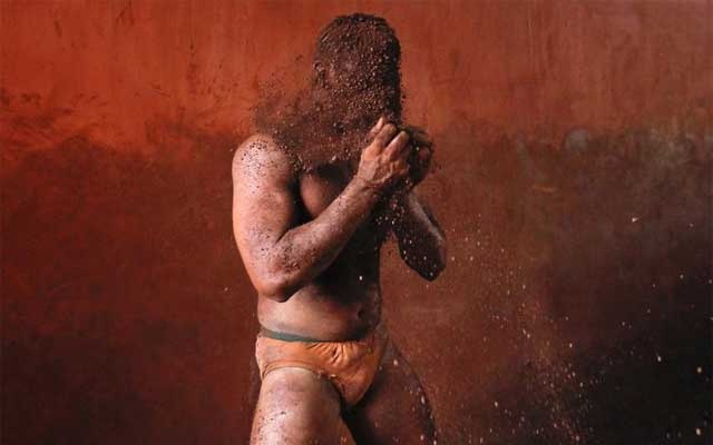 A wrestler rubs his hands with mud to prevent slipping due to sweat, during a traditional mud wrestling (Kushti) bout at the Akhaara centre in Kolhapur, about 400 kms south of Mumbai, Feb 14, 2012. Fewer people are taking up Kushti, according to the sport's coaches, as young athletes turn instead to mat wrestling to gain access to top international sports competitions. REUTERS/Danish Siddiqui