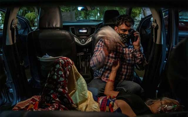 Manoj Kumar sits next to his mother, Vidhya Devi, who was suffering from a breathing problem as she receives oxygen support for free inside her car at a Gurudwara (Sikh temple), amidst the spread of the coronavirus, in Ghaziabad, India, Apr 24, 2021. REUTERS/Danish Siddiqui