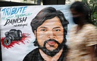 A woman walks past a painting of Reuters journalist Danish Siddiqui, after he was killed while covering a clash between Afghan security forces and Taliban fighters near a border crossing with Pakistan, outside an art school in Mumbai, India, Jul 16, 2021. REUTERS
