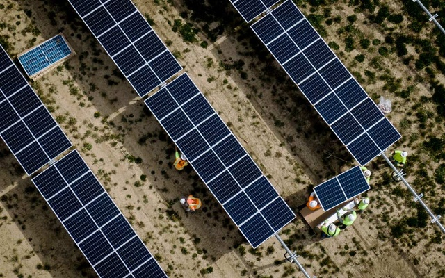 An aerial view of workers mounting panels at the nearly 2,000 acre Assembly Solar Project near Flint, Mich, May 19, 2021. The green economy is shaping up to look less like the industrial workplace that lifted workers into the middle class in the 20th century than something more akin to an Amazon warehouse or a fleet of Uber drivers: grueling work schedules, few unions, middling wages and limited benefits. Erin Schaff/The New York Times