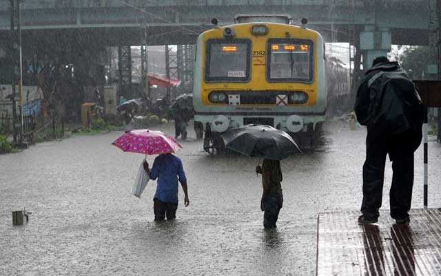 People cross inundated railway tracks next to a parked passenger train during heavy monsoon rains in Mumbai, India, June 9, 2021. REUTERS