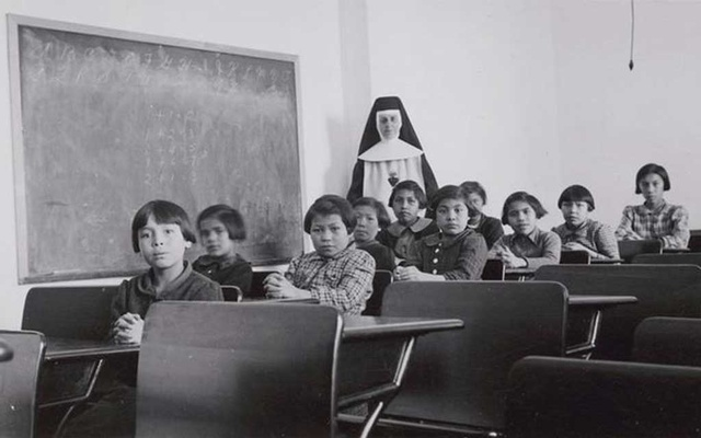 A group of female students and a nun pose in a classroom at Cross Lake Indian Residential School in Cross Lake, Manitoba in February 1940. Dept. Indian and Northern Affairs/Library and Archives Canada via Reuters