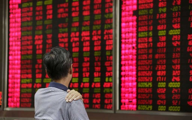 An investor looks at an electronic board showing stock information at a brokerage house in Beijing, August 27, 2015. REUTERS