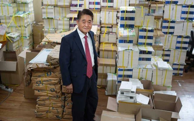 """Jee Man-won stands with copies of some of his books at his office in Seoul, South Korea, July 7, 2021. Jee calls the Gwangju uprising a """"riot"""" and says it was instigated by North Koreans. The New York Times"""